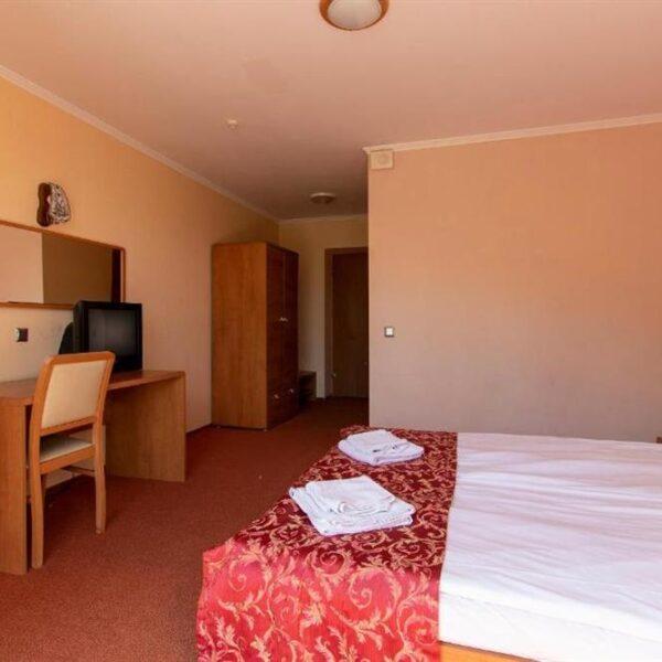 Широке двоспальне ліжко в номері готелю Терем