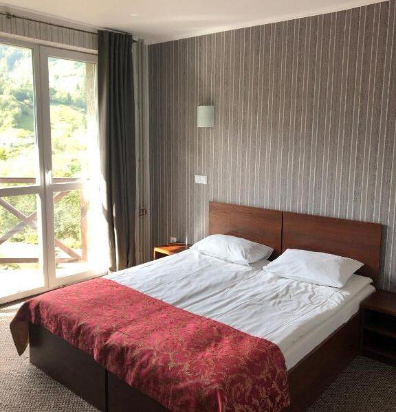 Широкая двуспальная кровать в современном номере отеля Терем
